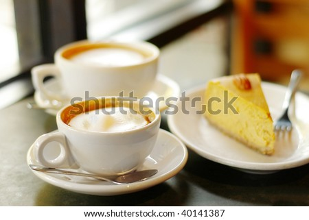 pair of cappuccino coffees and slice of pumpkin pie or pumpkin cheesecake - stock photo