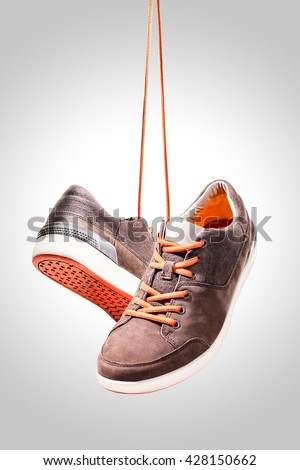 Pair of casual sport leather shoes hanging isolated on white background, Orange shoelace