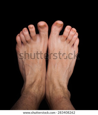 Pair of caucasian male feet isolated towards black - stock photo