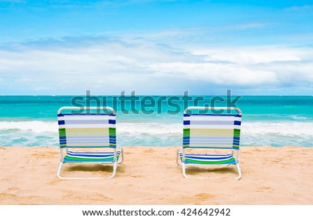 Pair of chairs on tropical sand beach.  - stock photo