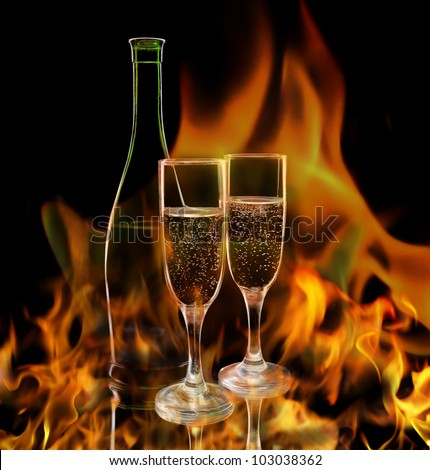 Pair of champagne flutes and wine bottle against a flame background - stock photo