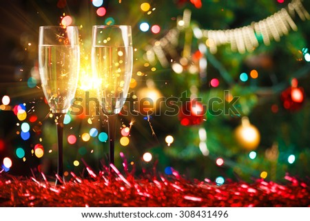 pair of champagne glasses and sparkler, Christmas tree ornament as the background - stock photo