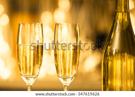 Pair of champaign glasses against a bright golden background.  - stock photo