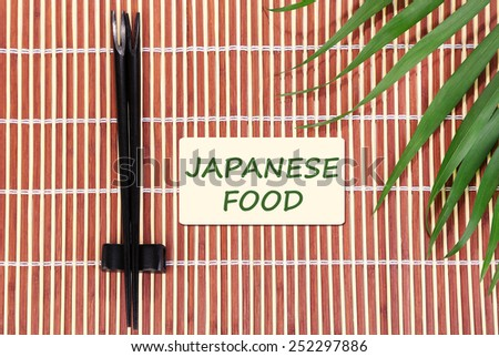 Pair of chopsticks and Japanese Food text on brown bamboo mat background - stock photo