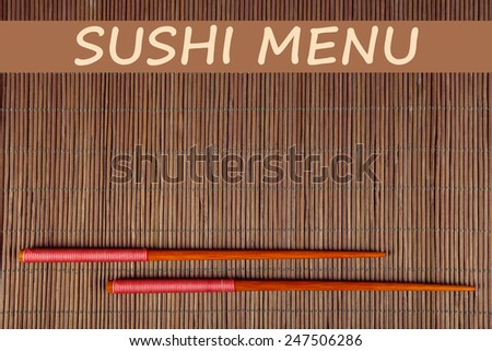 Pair of chopsticks and Sushi Menu text on brown bamboo mat background - stock photo