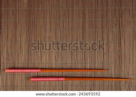 Pair of chopsticks on bamboo mat background
