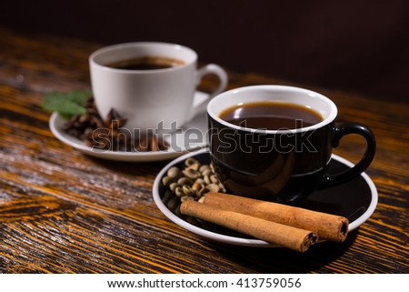 Pair of cinnamon sticks and beans in coffee cup saucer on dark stained wooden table