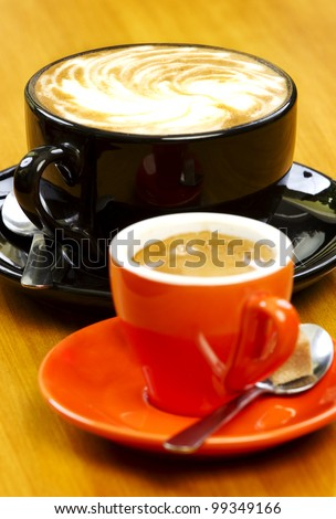 Pair of coffee drinks on wood table focus on cappuccino behind - stock photo