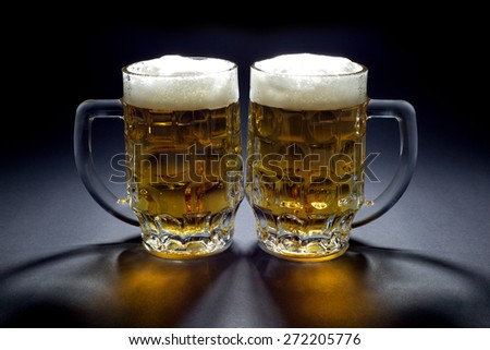Pair of Cold Beer Mugs Waiting for Someone to Drink Them - stock photo
