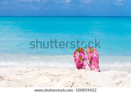 Pair of colored sandals on a white sand beach in front of the sea. The right place for relaxation and vacations