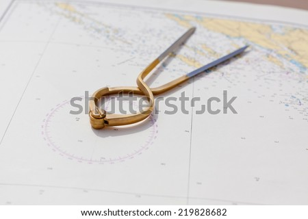 Pair of compasses for navigation on a sea map with low depth of field - stock photo