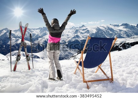 Pair of cross skis with woman skier hands up and sun-lounger, France high mountains.