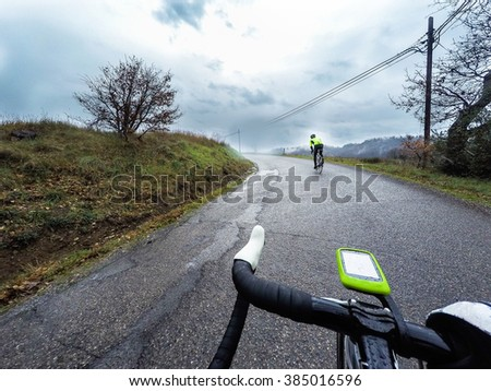 Pair of cyclists in an uphill road during a storm. POV Original point of view - stock photo