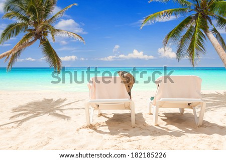 Pair of deck chairs between coconut palms on a tropical beach  - stock photo