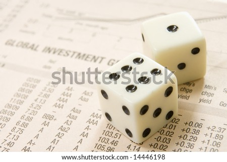 pair of dice with stocks and shares in background