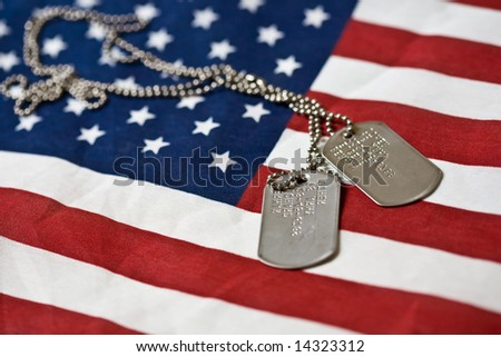 Pair of dog tags on american flag - stock photo