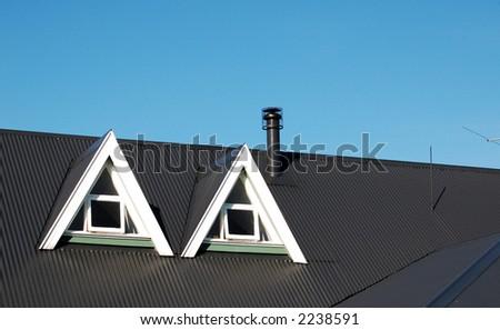 Pair of dormer windows in roof - stock photo