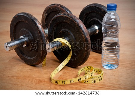Pair of dumbbells, measuring tape and bottle of water. Exercise and healthy diet concept. - stock photo