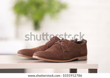 Pair of elegant male shoes against blurred background