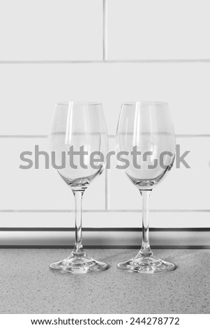 Pair of empty wineglasses against brick wall as a background - stock photo