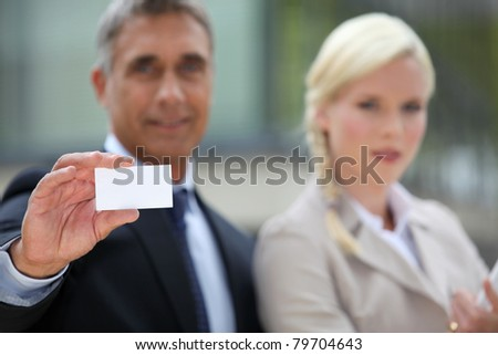 Pair of executives holding up a blank business card - stock photo