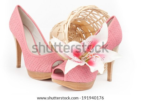 pair of fashionable pink high-heeled female shoes with lily and basket isolated over white - stock photo
