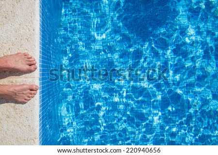 Pair of feet standing on stone border in front of swimming pool - stock photo
