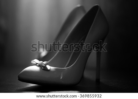 Pair of female amazing glamour classic stylish varnish leather luxurious wedding high-heeled shoes with pretty bow for modern sexy woman closeup black and white on gray background, horizontal picture  - stock photo