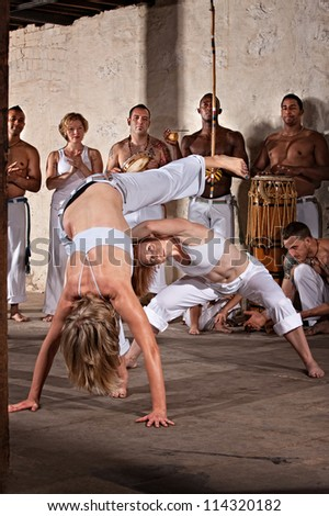 Pair of female capoeira practitioners performing with group - stock photo