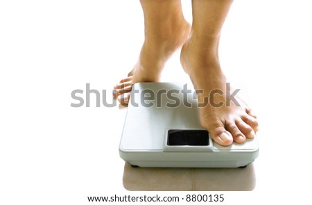 Pair of feminine feet about to stand on a weighing scale. - stock photo