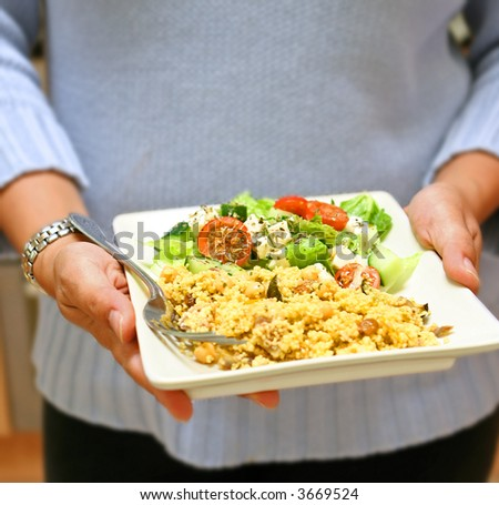 Pair of feminine hands holding a plate of moroccan savoury couscous with fresh greek salad with feta cheese and oregano. - stock photo