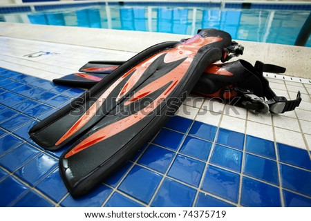 Pair of flippers at swimming pool - stock photo
