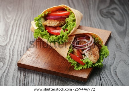 pair of fresh juicy tortilla wraps with chicken and vegetables, on table - stock photo