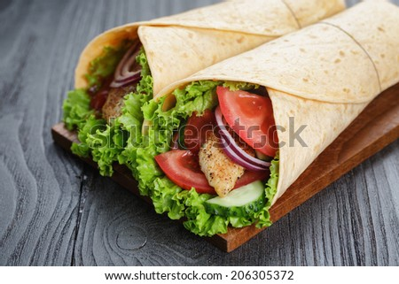 pair of fresh juicy wrap sandwiches with chicken and vegetables, on black wood table - stock photo