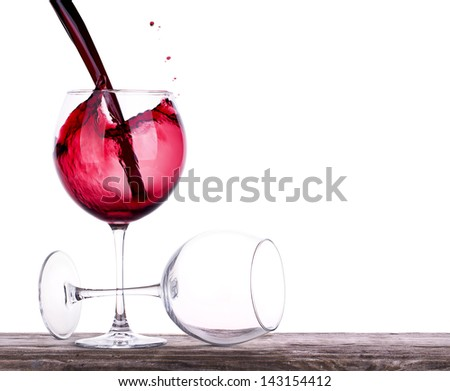 pair of full and empty wine glasses on a wooden table isolated on white - stock photo