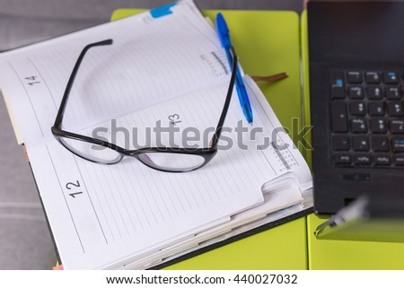 Pair of glasses lying on the laptop table near open blank page of a diary with a pen for making appointments, organising a schedule - stock photo