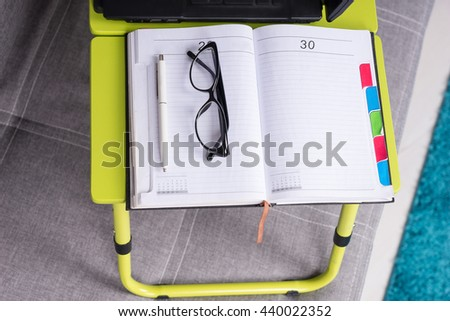 Pair of glasses lying on the open blank page of a business journal or diary with a pen for making appointments, organising a schedule or agenda - stock photo
