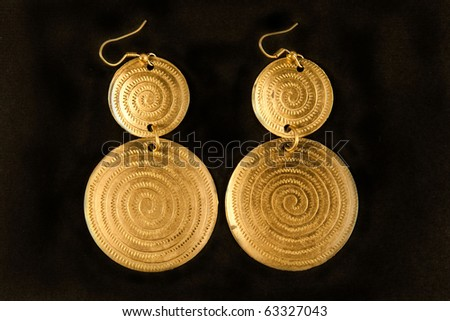 Pair of golden earrings placed on black - stock photo
