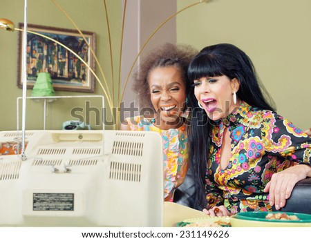 Pair of gorgeous woman enjoying television together - stock photo