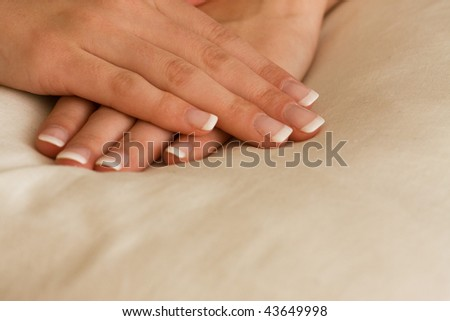 Pair of hands with french manicure on white background