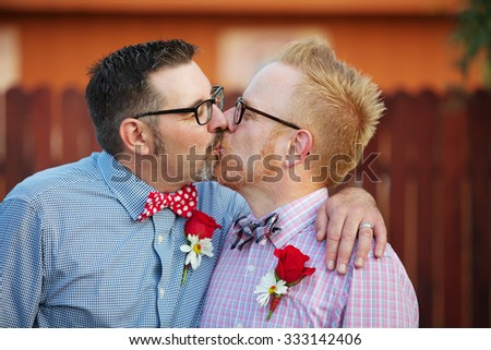 Pair of happily married gay men kissing outdoors - stock photo