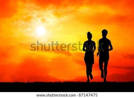 pair of healthy man and woman run together at sunrise silhouetted - stock photo