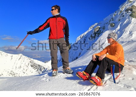 Pair of hikers talking while resting on snow covered summit  - stock photo