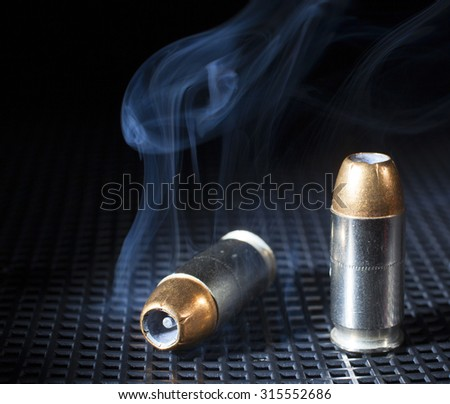 Pair of hollow point cartridges for a handgun and smoke - stock photo