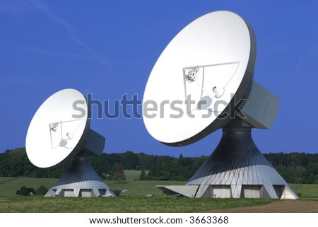 Pair of huge Satellite Dishes with blue sky and green grass - stock photo