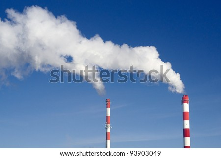 Pair of industrial chimneys with lots of smoke on a blue sky