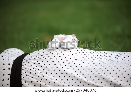 pair of kid's white shoes on mother's belly - stock photo