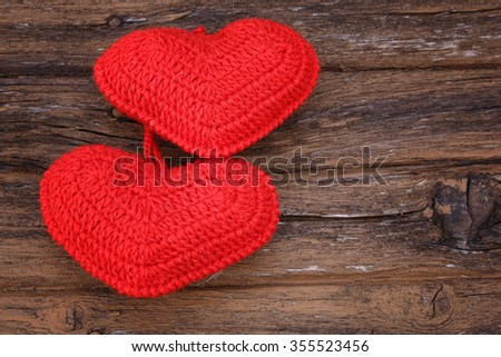 pair of knitted hearts on old wooden background Valentine's Day love handmade