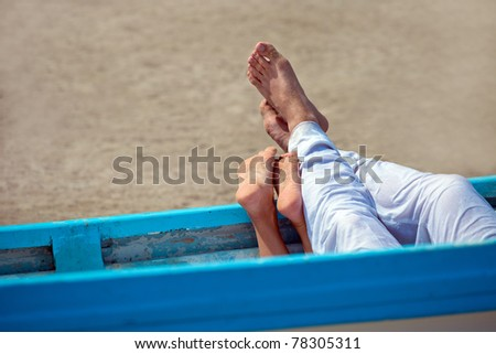 pair of legs in the boat on the beach - stock photo
