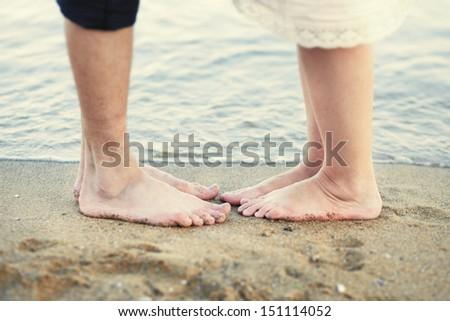 pair of legs on the beach - stock photo